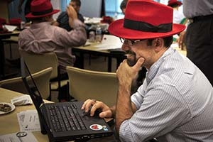 Man in fedora on computer