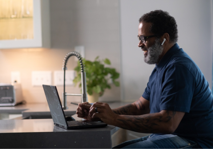 man working on laptop at the kitchen counter