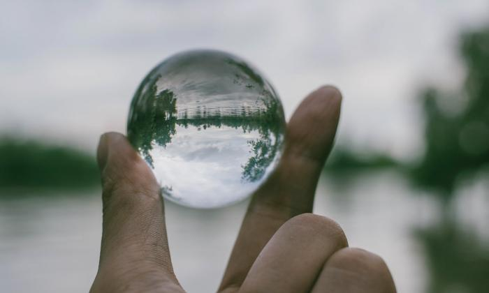 transparent ball showing landscape behind it.